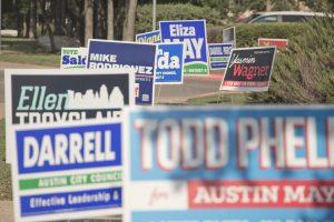 Political yard signs on a street corner in Austin, TX.